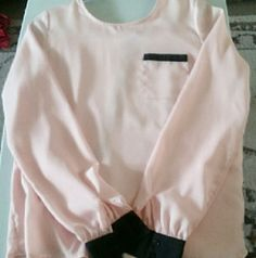 Dress shirt. Soft pink loose fitting dress shirt. Silky in the inside. Black cuffs. Buttons down in the back. Long sleeves. Charlotte Russe Tops Blouses