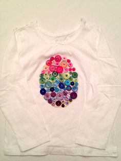 Last year I got Em a really cute shirt for St. Patty's Day. It had a green shamrock on the front with a few buttons attached. It was really cute and simple. I've been wanting to do this same idea for an Easter egg. Now that I have the time, I gave it a try. I should tell you, I love to sew.