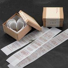 Inivitación en caja con papeles que forman corazón.