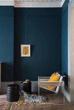 Profondeur et élégance des murs bleus, illuminés par un coussin jaune soleil (peinture Hague Blue, Farrow and Ball).