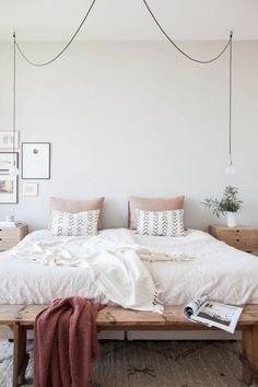 Bedroom set up with minimalist modern vibes, exposed wood, white walls.