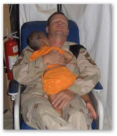 An American soldier comforting an injured child whose whole family has been murdered.  They slept in this chair for two days.  Love is what heals all wounds.
