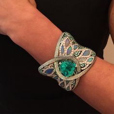 A Bracelet by Arunashi, centered with a 23 carat Paraiba Tourmaline and surrounded by Opals and Diamonds