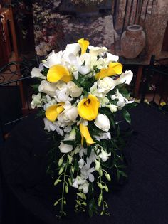 A Beautiful Cascading Bridal Bouquet of White Roses, White Dendrobium Orchids, Yellow Calla Lilies, and White Calla Lilies.