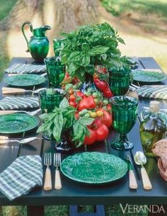 Only Carolyne Roehm would have thought of using basil plants and tomatoes as flower arrangements on a picnic table. Love the dishes, the napkins and cutlery.