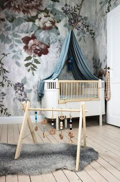 Adorable Scandinavian style nursery or kids room with flower wallpaper and wooden toys