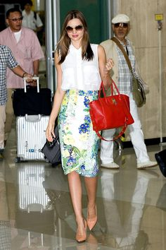 Miranda Kerr: musa, madre y top white with jellow and blue floreal nuaces skirt +white sleevelees shirt  blush pointy shoes+ red bag