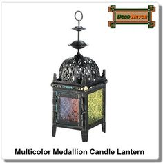 Multicolor Medallion Candle Lantern - Shimmering candlelight in a rainbow of colors will fill your room with style when you light the candle of your choice inside this iron candle lantern. It features a weathered black finish, intricate cutout design on the domed room, and a variety of colored pressed glass panels on each side.