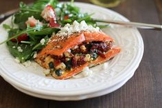 A recipe for salmon stuffed with sun-dried tomatoes, fresh basil, spinach and feta cheese. Includes substitutions and other serving suggestions.