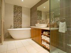 baddesign hölzerner waschtisch weiße tücher große badewanne badezimmerfliesen