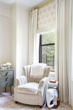 Chic bedroom boasts an upholstered art deco chair and an elephant side table placed under a window dressed in ivory pinch-pleat curtains layered over a white and gold roman shade.