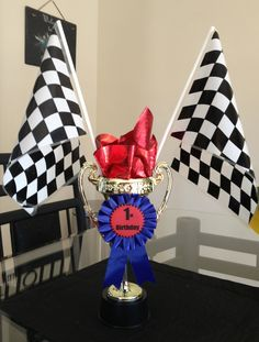 Race car trophy centerpiece: plastic trophies and flags from party city. Make ribbons say 1st birthday instead of 1st place. Fill with metallic paper.