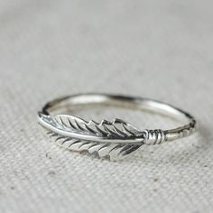 Sterling silver stacking feather ring. Light and easy for every day wear. A great little ring to stack or wear alone. The feather and band are solid sterling silver. The focal measures one half inch long and it is set on a hammered sterling band and custom made to fit you. Please allow me a couple of weeks to make this for you. This is customized for your size so please allow me up to two weeks to make it for you. This ring is available from size 2 to 12 in whole and half sizes. Please…