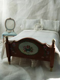 A beautiful antique style bed, hand painted with flowers, vines and bouquets. The bed is made up with linens hand made from antique French fabrics and lace. The bedding includes; mattress flat sheet embroidered top sheet bolster bolster cover two pillows two pillow cases an