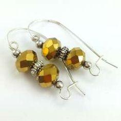 Kolczyki ze złotymi kryształkami szklanymi na dużych biglach.