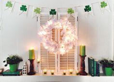 Pre-lit white Christmas wreath, shamrock garland, and green candles on a mantel--Jennifer Lutz