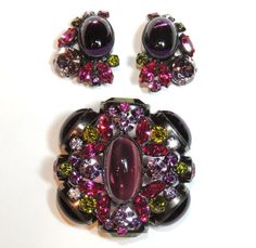 "Absolutely gorgeous unsigned Schreiner brooch with matching earrings. Guaranteed Schreiner. Obvious Schreiner construction characteristics. Sawtooth bezels. Point up, reverse set rhinestones. Eyelet connectors. Gun metal finish. Domed, multi layer rhinestones. The brooch measures 2"" x 2"". The clip back earrings measure 7/8"" x 1&1/4"". Plum, magenta and olivine green glass stones. All stones are present and original. Exclusively on Ruby Lane"