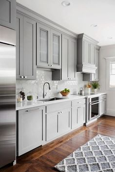 Exquisite gray kitchen features a gray trellis rug placed in front of a stainless steel sink paired with a satin nickel gooseneck faucet fixed in front white honeycomb backsplash tiles to a white quartz countertop accenting gray cabinets with polished nickel hardware.