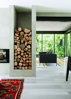 Fireplace with stone built-in storing firewood, grey floors, and a red feature rug