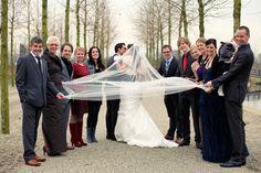 vrolijke familie foto met bruidspaar in park Vleuten waarbij iedereen de sluier vast houdt