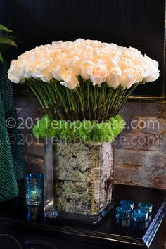 Putting a birch log in a clear vase filled with long-stemmed roses makes for a dramatic centerpiece.