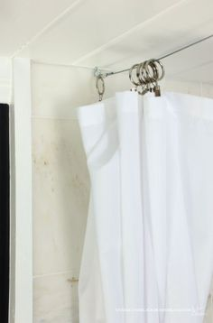 30 cent per foot wire rope, eye hooks, and curtain clips make a custom curtain rod alternative.
