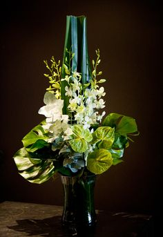 Unknown designer. white dendrobium orchid, variegated monstera leaves. green and white anthuriums, tall whalebone leaves