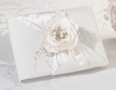 Family and friends will find this elegant guest book covered in cream satin as they arrive at the reception. To give this guest book its unique look, a hand crafted flower with a pearl/rhinestones orn