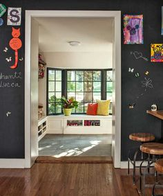 A generous opening connects the kitchen (whose walls are painted in chalkboard paint) with the mudroom to reveal an array of handy  built-in benches with storage beneath.