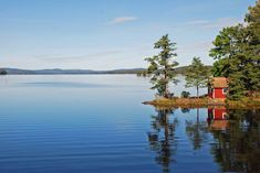 Photo about A lake in Sweden with reflection of the red house and trees in the water. Scenic view of hills along the edge of the lake and blue skies above. Image of landscape, calm, vegetation - 3217823 Camping Am See, Camping Cot, Van Camping, Camping Chairs, Camping Gear, Voyage Suede, Haus Am See, Landscaping Images, Summer Books