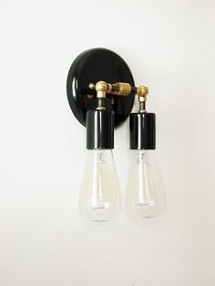 This double black and brass wall sconce lamp is a unique design piece handmade and handcrafted in our studio with sustainable materials. An elegant