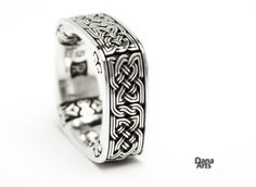 Celtic knot band with a beautiful knot that is on all four sides of the square band. The knot has a thin groove that makes it look even more intricate. The flower like pattern and swirls on the inside make this design truly unique. The black patina background lets the details of the ring