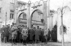 German Order Police and Jewish residents of the Krakow Ghetto are photographed in front of the ghetto gate. The purpose of the photo is unclear, although the Germans missed no opportunity to photograph their victims and, even better, take photos of themselves with the various hapless people they tortured and killed.