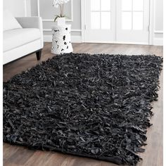 Strips of soft, genuine leather highlight this hand-tied shag rug. This area rug features warm black tones.