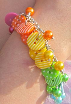 A bright rainbow of stripy and spotty buttons on a bracelet chain with matching glass pearls, lots of fun to wear!  $18.50