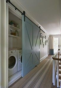 Closet Laundry Room with Barn Door. Barn Door Laundry Room. Second floor landing features concealed laundry room hidden behind blue barn door as well as brown and blue striped runner. Hall laundry room with open cubbies over white front-load washer and dryer next to wall of photos and French doors covered in two-tone curtains. #BarnDoor #Laundryroom Brooks and Falotico.