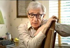 By his beloved typewriter, while being interviewed by Robert Weide for Woody Allen: A Documentary
