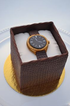 """Watch Box - A mini cake for a co-worker who loves watches. The """"box"""" was made with modelling chocolate. The """"rope"""" is also modelling chocolate and I pushed it through my extruder to give it a velvet look. Everything else was fondant."""