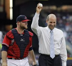 Smoltz holds the ball after throwing out the ceremonial first pitch to the catcher Brian McCann #16 before the game against the Toronto Blue Jays