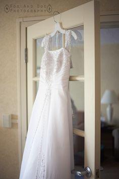 Elegant wedding dress hanging from a windowed door