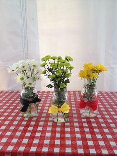 Simple centerpieces with colored daisies and tied off with a cute ribbon.
