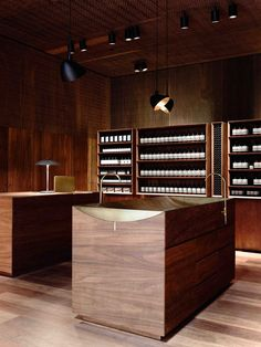 Panels of gum wood in a variety of tones and textures cover surfaces in this Aesop store.