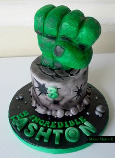6 in chocolate cake with hulk colored white chocolate buttercream and covered in fondant. The fist is make out of rice krispies and covered with modeling chocolate and fondant. Air-brushed and hand painted!