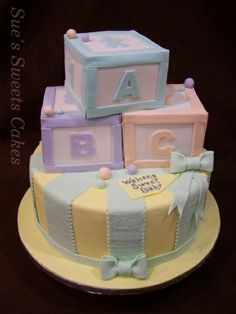 This beautiful baby shower cake features pastel baby blocks that were carved out of cake. Yellow fondant with pale green ribbons and bows accented the cake as well. The delicious cake was moist red velvet filled with cream cheese icing.