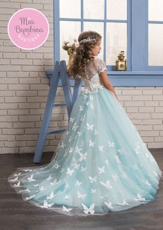 The Aurora is a flower girl dress with beautiful white lace overlayed bodice with short lace scalloped sleeves and a multi-layered tulle skirt. Lovely butterflies train extending from the waistline ad