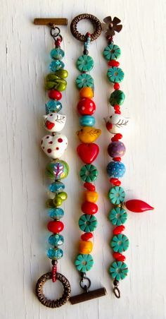 Songbeads {inspiration only. so cute to pair the cool blues with these intense primary reds and yellows, and mix in the figural /bird/heart/ beads}