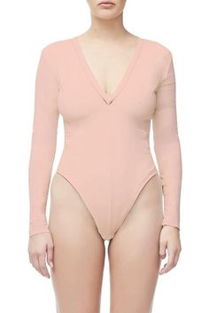 f2f7d0f003 Blush deep-v long sleeve bodysuit with sheer trim around neckline. All  bodysuits include a GOOD AMERICAN pouch and pasties for easy wear.