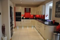 High Gloss cupboards, dark counter, tiles maybe too bright - a more toned down red?