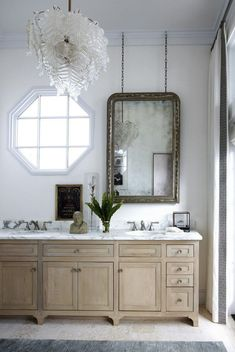Along with a striking Venetian glass chandelier, a master bathroom in a Florida home features double sinks with fittings by Rohl, custom-made cabinetry, and a silver-leafed mirror by Eloquence.