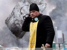 A priest holds a cross and shield during clashes between protesters and police in Kiev by Sergey Gapon